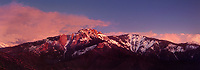 977000001 panoramic view- sunset light turns snow covered castle rock and the surrounding mountain top a soft reddish gold with clouds framing the mountain in sequoia national park in california