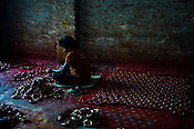A worker paints the earthen pots in a workshop in Kumhartuli in Kolkata, West Bengal, India.