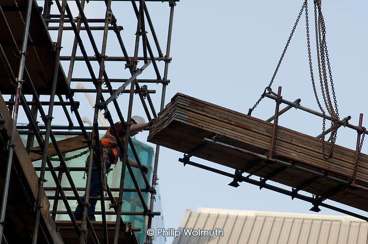 A scaffolder unloads planks lifted by crane on a building undergoing demolition at the Barbican in the City of London.