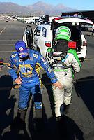 Nov. 11, 2012; Pomona, CA, USA: NHRA funny car driver Jack Beckman (right) walks past teammate Ron Capps during the Auto Club Finals at at Auto Club Raceway at Pomona. Mandatory Credit: Mark J. Rebilas-