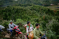 A group of villagers drive motorcycles along a muddy track in the Hoang Lien Son National Park as they head to a Black cardamom (Thao Qua) plantation to harvest the crop.