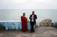 A Tibetan female monk and a local Han businessman near to Qinghai Lake. Qinghai Lake, China's largest inland body of water lies at over 3000m on the Qinghai-Tibetan Plateau. The lake has been shrinking in recent decades, as a result of increased water-usage for local agriculture. Qinghai Province. China. 2010