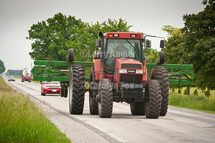 1996 Case IH 7250 tractor driving down the road with an implement in tow