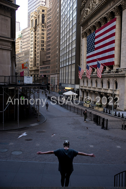 """New York, New York<br /> April 4, 2020<br /> <br /> A woman uses the Federal Hall stairs to exercise with the New York Stock Exchange closed and street void of tourists. <br /> <br /> The corona virus has transformed urban architectural spaces with fear of proximity. Not entirely void of humanity, social distancing, within expansive city environments has created a landscape of aggrandizing physical structures and expanding spaces while diminishing the scale of humans. Face masks enhance the anonymity of """"the person"""", reducing them to a figure or an uninterrupted shadow falling on a surface."""