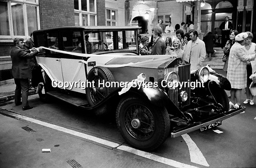 Caxton Hall Westminster London. Tying a white ribbon, a good luck ritual around the hired Rolls Royce car. 1970s 1972 London . ..