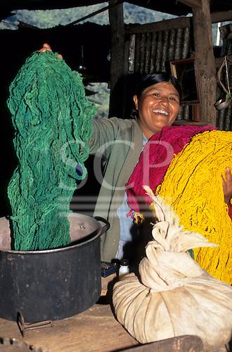 Urubamba Valley, Peru. Smiling Quechua woman showing her freshly dyed wool skeins.