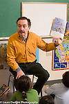 Elementary School male teacher reading to Grade 3 class