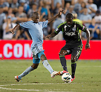 Julio Cesar (55) of Sporting Kansas City tackles the ball away from Eddie Johnson (7) of the Seattle Sounders during the game at Livestrong Sporting Park in Kansas City, Kansas.   Sporting Kansas City won the Lamar Hunt U.S. Open Cup on penalty kicks after tying the Seattle Sounders in overtime.