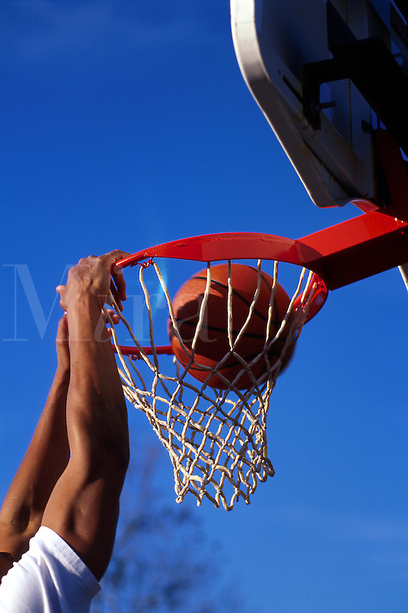 The hands of a male basketball player linger on the rim of a hoop after he dunked the ball.