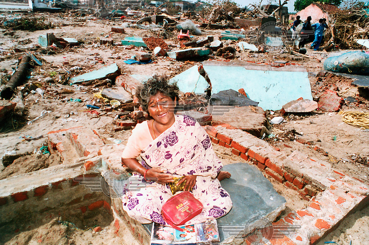 A grieving woman sits in the ruins of her home following the tsunami which struck South Asia on 26/12/2004..An underwater earthquake measuring 9 on the Richter scale triggered a series of tidal waves which caused devastation when they struck dry land. 12 countries were affected by the tsunami, with a combined death toll of over 150,000.