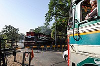 INDIA, Madhya Pradesh, Nimad region, Khargone, Railroad Crossing with closed barriers, running train, diesel locomotive