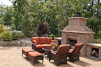Outdoor fireplace fire pit on patio with furniture makes for a sense of an outside living room in the garden for upscale lifestyle