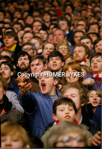 Football fans 1980s UK. Crowd of faces, group of male and one female supporter, Anfield football stadium Liverpool.  Supporters in the Kop - single tier terraces and stands watching match.