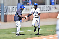 Asheville Tourists left fielder Mylz Jones (7) shakes hands with Mike Devereaux (12) as he rounds the bases after hitting a walk off home run during a game against the Charleston RiverDogs at McCormick Field on July 10, 2016 in Asheville, North Carolina. The Tourists defeated the RiverDogs 4-2. (Tony Farlow/Four Seam Images)