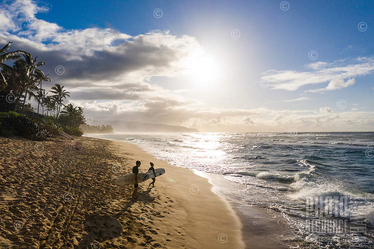 A couple head out to surf towards sunset at Laniakea, North Shore of O'ahu.