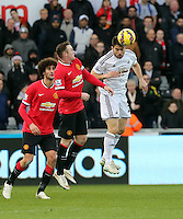 SWANSEA, WALES - FEBRUARY 21: Jordi Amat (R) heads the ball away from Wayne Rooney of Manchester United during the Barclays Premier League match between Swansea City and Manchester United at Liberty Stadium on February 21, 2015 in Swansea, Wales.