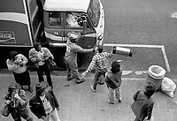 A white man attacks a black Coca-Cola delivery man on the sidewalk in Hillbrow towards the end of the apartheid era. Everybody stands and watches.