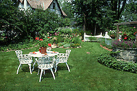 Summer Garden with white wrought iron furniture table and chairs, perfect lawn grass and old house, wishing well in yard, flowers, picket fence for beautiful backyard living. New Jersey.