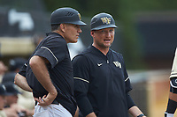 Wake Forest Demon Deacons head coach Tom Walter (left) chats with volunteer assistant coach Wake Forest Demon Deacons volunteer assistant Joey Hammond (right) during the game against the Miami Hurricanes at David F. Couch Ballpark on May 11, 2019 in  Winston-Salem, North Carolina. The Hurricanes defeated the Demon Deacons 8-4. (Brian Westerholt/Four Seam Images)