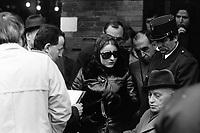 """Picard, Me Cathala, Me Bouscatel, Me Rastoul"""". Place Wilson. 30 novembre 1976. Vue d'ensemble de personnes en train de discuter (plan taille). De g. à d. : Me Bouscatel de dos (avocat de José Picard), homme de profil tenant un dossier (juge d'instruction M. Ducasse?)femme avec lunettes noires et foulard sur la tête, policier. Cliché pris le jour d'une reconstitution judiciaire dans le cadre de l'affaire du meurtre de René Trouvé. Observation: Affaire René Trouvé-Birague : le 19 février 1976, le journaliste René Trouvé est assassiné d'une balle dans la tête, par deux inconnus, alors qu'il regagne son domicile au 33 rue Bayard."""