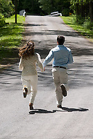 Man and woman running on country road<br />
