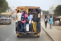 Senegal. Dakar. A public Renault minibus fully loaded with its back door open carries extra passengers, most of them students on their way to school. 07.12.09  © 2009 Didier Ruef