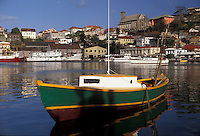 "AJ2526, Grenada, Caribbean, St. George's, Caribbean Islands, Green fishing boat anchored in the calm waters of the Carenage Harbor with a scenic view of St. George's the capital city on the steep hillside on the island of Grenada """"the spice isle"""" (a British Commonwealth member)."