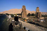 Tourists visiting the Colossi of Memnon, two massive stone statues of Pharaoh Amenhotep III, in the Theban necropolis, Luxor, Egypt.