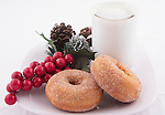 Donuts are served with a cup of coffee with whipped cream. Holiday decorations decorate the plate.