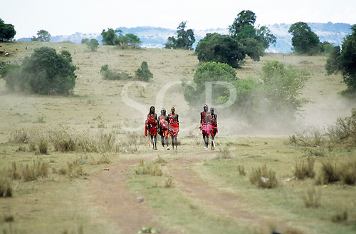 Lolgorian, Kenya. Group of Moran warriors wearing traditional red shukka wraps on a track at the Eunoto coming of age ceremony.