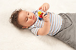 5 month old baby boy closeup on back holding toy using both hands