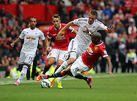 Pictured: Gylfi Sigurdsson of Swansea (C) against Adnan Januzaj (L) and tackled by Ashley Young (R) of Manchester United. Saturday 16 August 2014<br />