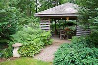 Garden lath house gazebo building, ferns, ornament, shrubs, furniture table and chairs, hostas, lawn grass, trees