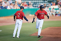 Heriberto Hernandez (11) of the Charleston RiverDogs slaps hands with third base coach Blake Butera (3) after hitting a home run against the Augusta GreenJackets at Joseph P. Riley, Jr. Park on June 25, 2021 in Charleston, South Carolina. (Brian Westerholt/Four Seam Images)