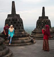 Borobudur, Java, Indonesia.  Indonesian Woman Photographing Young Couple.