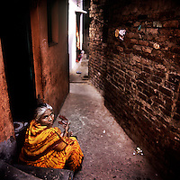 A woman sits in front of her home in the Kathputli Colony. Located in northwest Delhi, Kathputli is inhabited by approximately 2,000 performing artists, practicing traditional art forms such as marionette puppetry, juggling, magic, acrobatics, dance and music. Many have travelled all over the world showcasing their abilities, but they still choose to remain living in this slum, which is one of the most impoverished in the city.