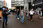 A Newcastle fan being filmed by a passing TV cameraman outside St James Park. Newcastle v West Ham, August 15th 2021. The first game of the season, and the first time fans were allowed into St James Park since the Coronavirus pandemic. 50,673 people watched West Ham come from behind twice to secure a 2-4 win.