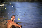 Xingu Indigenous Park, Brazil. Sting sitting beside the river with butterflies around him; Nov 1990.