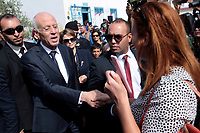 Tunisia's presidential candidate Kais Saied wave to supporters as he leaves a polling station in the capital Tunis on October 13, 2019 during the second round of the presidential election.