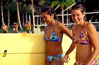 Two teenaged girls share a moment of laughter as they prepare to take a surfboard back into the ocean.