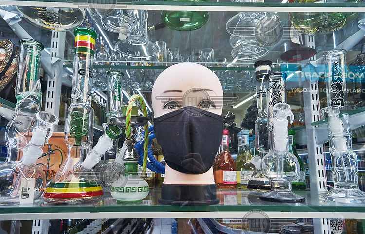 A mannequin head wearing a face mask displayed in the window of a grocery shop selling water pipes.
