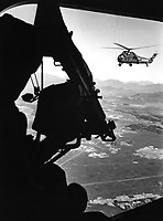 Vietnam:  helicopter and soldier approaching target.  Ca. 1965.<br /> EXACT DATE SHOT UNKNOWN<br /> NARA FILE #:  306-PSC-65-4106<br /> WAR & CONFLICT BOOK #:  402
