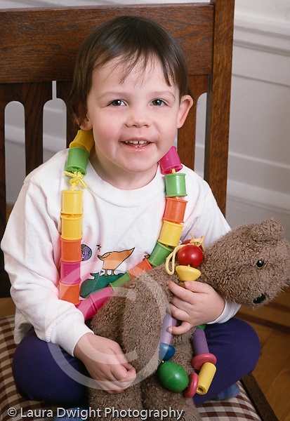 portrait of 3 year old girl smiling at camera holding favorite stuffed animal toy bear wearing colorful plastic spools necklace Caucasian vertical