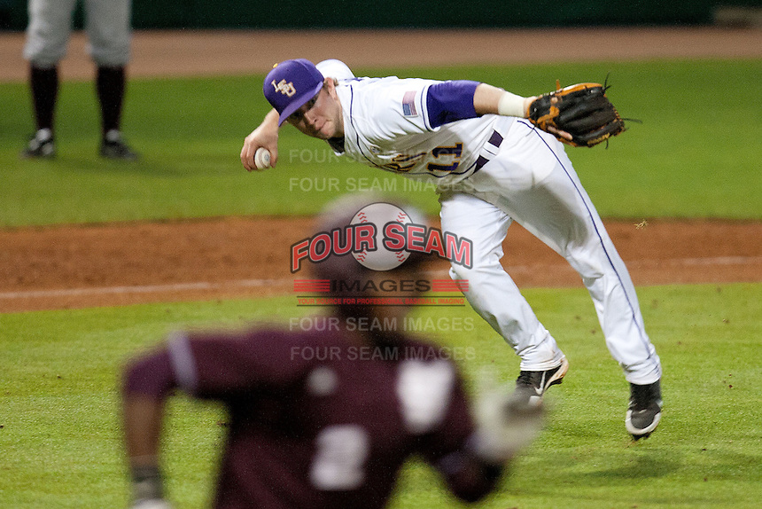 LSU Tigers third baseman Tyler Hanover #11 fields a bunt to make an outstanding defensive play against the Mississippi State Bulldogs at the NCAA baseball game on March 16, 2012 at Alex Box Stadium in Baton Rouge, Louisiana. LSU defeated Mississippi State 3-2 in 10 innings. (Andrew Woolley / Four Seam Images)..