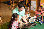 Education Preschool Headstart young male teacher reading piture book to group of three girls