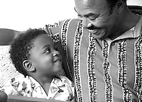 African-American Father with Son, smiling; hugging; affection, family activities, parents, children, Black child, man, black and white image. Dave Johnson, Gus Hoffman. Colorado, home.