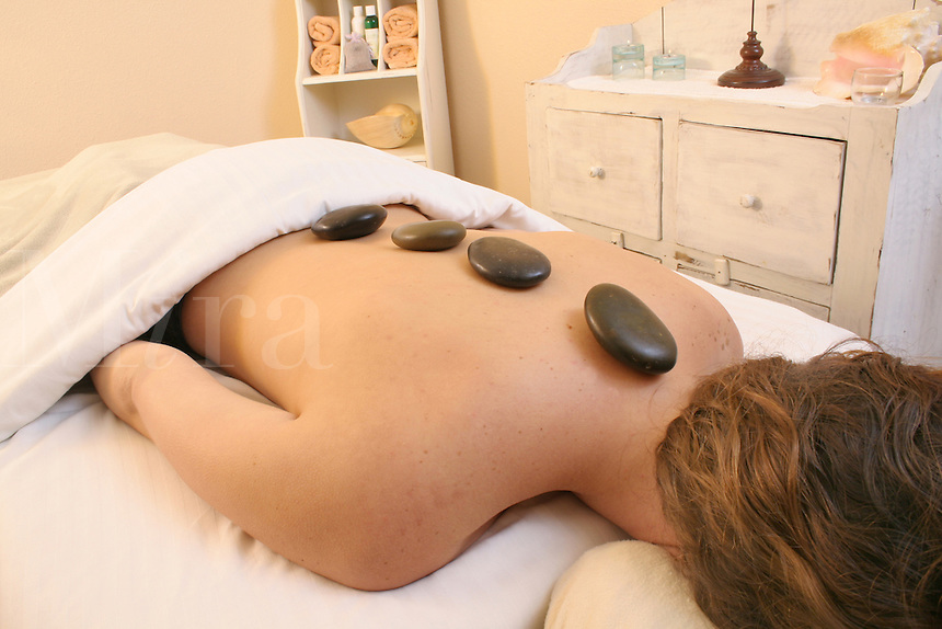 Released health spa woman heated stones on back