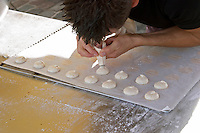 Making macarons almond bisquits, typical of Bordeaux and Saint Emilion. On a street market. Bordeaux city, Aquitaine, Gironde, France