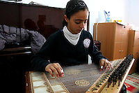 """FOR FAOIROUZ SONG """"THE FLOWER OF THE CITIES"""" - A Palestinian girl plays the Kanoun during a lesson in the Edward Said National Conservatory of Music in East Jerusalem. Photo by Quique Kierszenbaum."""