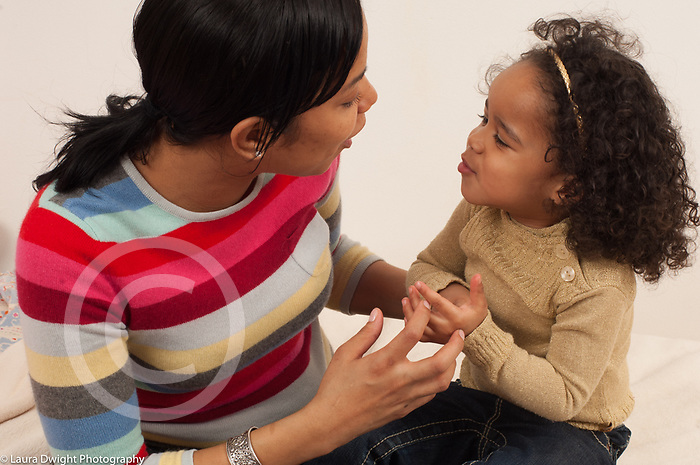 mother talking with toddler daughter just turned 3 years old sitting on bed, both gesturing horizontal